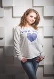 Портрет молодой курчавой женщины в джинсах представляя против белой стены Стоковые Фотографии RF