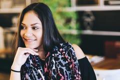Портрет молодой мечтая девушки в кафе Красивая девушка сидит в кофейне и взгляды, девушка усмехаясь, вручают около стороны Стоковые Фото