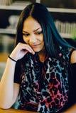 Портрет молодой мечтая девушки в кафе Красивая девушка сидит в кофейне и взгляды, девушка усмехаясь, вручают около стороны Стоковое Изображение