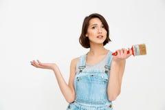 Портрет молодой милой девушки, смотрящ изумленный, держа paintin Стоковые Фотографии RF