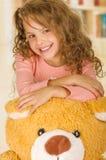 Портрет молодой милой девушки усмехаясь и представляя над ее головой плюшевого медвежонка s в предпосылке офиса доктора стоковое фото