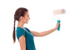 Портрет молодой милой женщины здания брюнет в форме с роликом краски в изолированных руках делает реновацию на белизне Стоковое Изображение RF