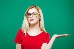 Портрет молодой милой женщины при длинные светлые волосы, Eyeglasses и красный верх держа пустой космос на ее руке на зеленом цве Стоковые Изображения RF