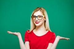 Портрет молодой милой женщины при длинные светлые волосы, Eyeglasses и красный верх держа пустой космос на ее 2 руках дальше Стоковое фото RF