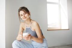 Портрет молодой нежной девушки усмехаясь держащ чашку смотря камеру сидя на стуле над белой стеной в самом начале утро Стоковое Изображение RF