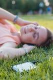 Портрет молодой привлекательной девушки слушая к музыке с наушниками Стоковые Фото