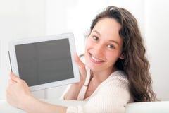 Портрет молодой привлекательной женщины используя таблетку на софе Стоковые Изображения RF