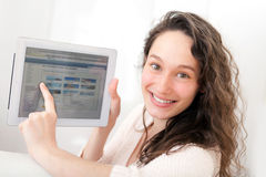 Портрет молодой привлекательной женщины используя таблетку на софе Стоковое Изображение