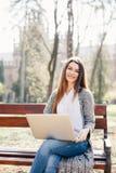 Портрет молодой профессиональной женщины используя портативный компьютер пока сидящ на стенде в парке, на солнечный день Стоковые Фотографии RF