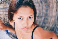 Портрет молодой сексуальной красивой девушки сидя на гамаке ротанга, расплывчатой предпосылке Стоковые Фотографии RF