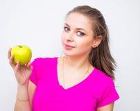 Портрет молодой симпатичной женщины нося в розовой рубашке с зеленым яблоком Стоковое Фото