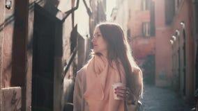 Портрет молодой стильной женщины на утре смотря вокруг Счастливая девушка исследует старые улицы и выпивая кофе стоковое фото rf