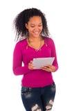 Портрет молодой счастливой африканской женщины используя таблетку цифров стоковое фото