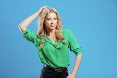 Портрет молодой счастливой блондинкы, непринужденного стиля, голубой предпосылки Стоковое Изображение RF