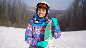 Портрет молодой, счастливой девушки с сноубордом в ее руках День зимы солнечный, вокруг горы, лыжный курорт A акции видеоматериалы