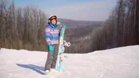 Портрет молодой, счастливой девушки с сноубордом в ее руках День зимы солнечный, вокруг горы, лыжный курорт A видеоматериал