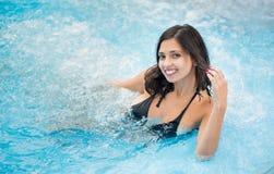 Портрет молодой счастливой женщины в черном купальном костюме с снег-белой улыбкой наслаждаясь в джакузи Стоковое Изображение RF