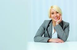 Портрет молодой счастливой коммерсантки сидя на таблице Стоковые Фотографии RF