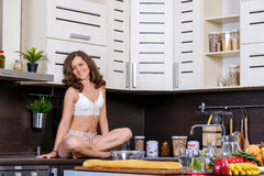 Портрет молодой тонкой женщины в женское бельё в кухне Стоковая Фотография