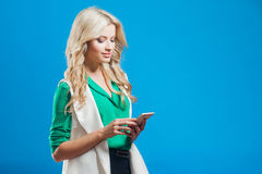Портрет молодой уверенно блондинкы, использует телефон, голубую предпосылку Стоковые Фотографии RF
