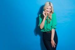 Портрет молодой уверенно блондинкы, непринужденного стиля, голубой предпосылки Стоковая Фотография RF