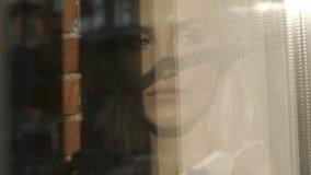 Портрет молодой унылой женщины смотря через окно сток-видео