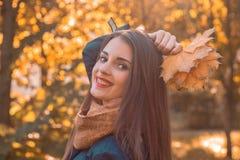 Портрет молодой усмехаясь девушки в парке осени с листьями в руке, конце-вверх Стоковые Изображения