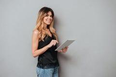Портрет молодой усмехаясь девушки используя планшет Стоковые Изображения