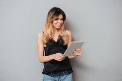 Портрет молодой усмехаясь девушки используя планшет Стоковое фото RF