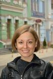 Портрет молодой усмехаясь девушки на предпосылке городских домов. Стоковая Фотография RF