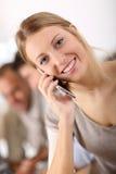 Портрет молодой усмехаясь женщины используя smartphone Стоковые Фотографии RF