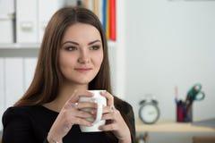Портрет молодой усмехаясь коммерсантки сидя на ее офисе Стоковые Фото