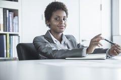 Портрет молодой усмехаясь коммерсантки сидя на таблице и держа ручку, смотря камеру Стоковая Фотография RF