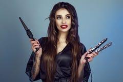 Портрет молодой усмехаясь модели при совершенные зубы и peignoir длинных волос нося silk держа завивая раскручиватель палочки и в Стоковое фото RF