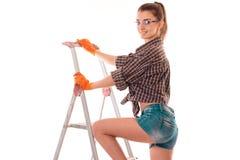 Портрет молодой чувственной женщины здания брюнет с лестницей делает реновацию и усмехаться на камере изолированной на белизне Стоковая Фотография RF