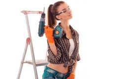 Портрет молодой чувственной женщины здания брюнет с закрытыми глазами и сверлит внутри изолированные руки делает реновацию на бел Стоковые Фотографии RF