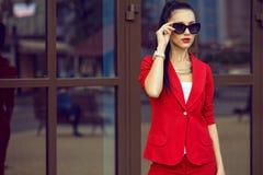 Портрет молодой шикарной темн-с волосами коммерсантки в стильных солнечных очках и ярком красном костюме Стоковое Фото