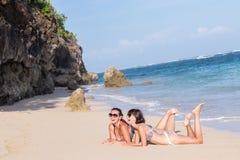 Портрет 2 молодых женских друзей лежит на береге моря смотря камеру и смеяться над Кавказские молодые женщины Стоковое фото RF