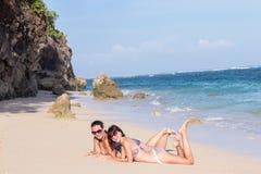 Портрет 2 молодых женских друзей лежит на береге моря смотря камеру и смеяться над Кавказские молодые женщины Стоковое Изображение