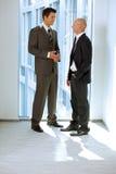 Портрет молодых кавказских бизнесменов говоря в офисе Стоковое Изображение