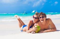 Портрет молодых пар лежа на тропическом пляже в Барбадос и выпивая коктеиль кокоса Стоковые Фотографии RF