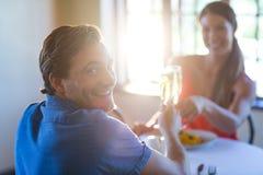 Портрет молодых пар провозглашать каннелюры шампанского пока имеющ обед Стоковые Изображения RF