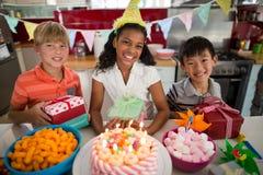 Портрет молодых друзей празднуя день рождения в кухне Стоковые Фотографии RF