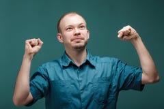 Портрет молодых успешных усмехаясь докторов поднимает его руки вверх на голубой предпосылке Жест победы стоковые изображения rf