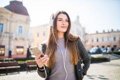 Портрет моды образа жизни молодой стильной женщины битника идя на улицу слушает музыка Стоковое фото RF