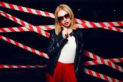 Портрет моды сексуальной девушки с конфетой в руке нося стиль утеса, солнечные очки на предпосылке предупреждающей ленты Стоковое фото RF