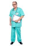 Портрет мрачного ого доктора держа доску сзажимом для бумаги стоковая фотография