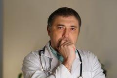 Портрет мужского доктора с рукой на подбородке стоковые фотографии rf