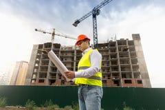 Портрет мужского инженера по строительству и монтажу стоя на строительной площадке и смотря светокопии Стоковая Фотография RF