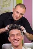 Портрет мужского клиента получая его волосы помыл на салоне Стоковое фото RF